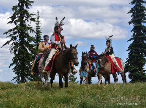 """Nez Perce riders in native costume at the """"Indian Post Office,"""" an ancient traveler's landmark on the Lolo Trail."""